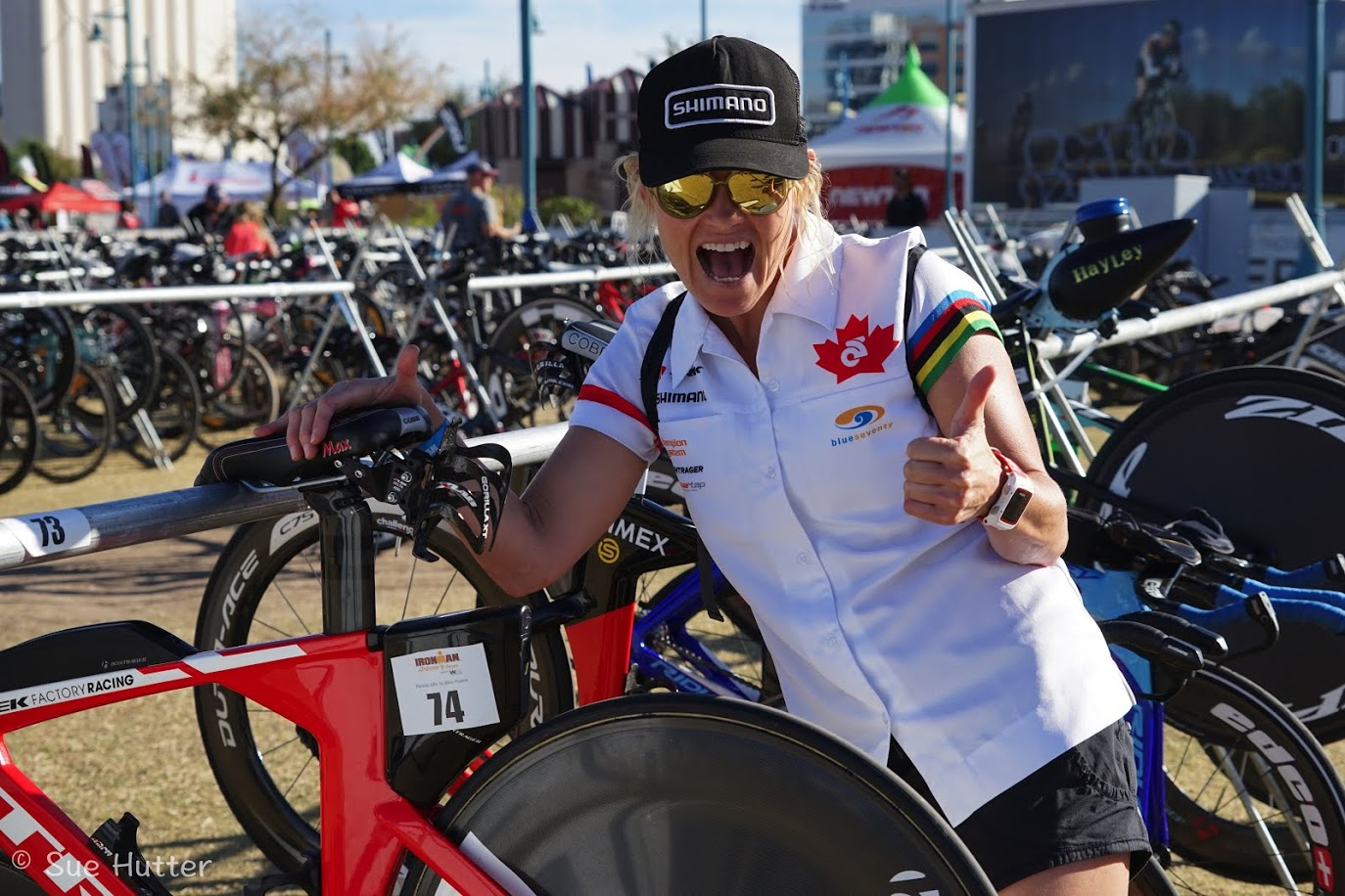 triathlete melanie mcquaid excited pre race Ironman Arizona with her Trek bike and Rudy Project glasses in transition